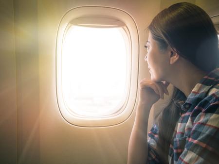 真剣に、甘い女性の写真は夕焼け空の風景を表示します。旅行者は概念を探して快適なキャビンの座席に座っています。