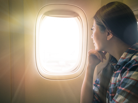 photo of sweet lady seriously view scenery of sunset sky. traveler sitting on the comfortable cabin seat looking out concept.