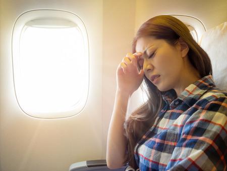 カジュアルなスタイルの服の女性を身に着けている頭の痛い感じの飛行機に乗るし、不快な額エクスプレスに置く手します。