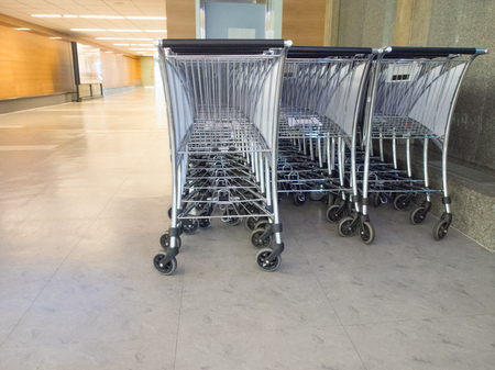 three row of luggage cart parking at modern international airport corridor offer all traveler using for carry big bag.