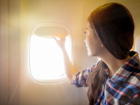 Despegue y aterrizaje del avión la ventana debe abrirse. Sonriente niña abierta mirando fuera del paisaje con el tiempo soleado sensación agradable. Foto de archivo - 83943865