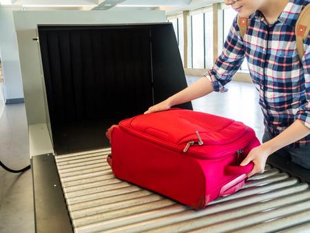 Glückliche asiatische chinesische reiseleute mit scanner setzen koffer auf gürtel von röntgengerät am flughafen internationales Sicherheitskontrollkonzept. Standard-Bild - 83943866