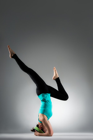 pretty yoga fitness coach woman using handstand posing to stretching legs and workout personal body muscle in grey background.