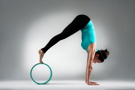Professeur de gymnastique élégant mains inversées support corps sur le sol et les jambes sur la bague pilates avec corps extensible développer la douceur dans le studio de fond de mur gris. Banque d'images - 83992645