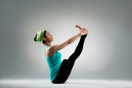 permanence: side picture of young gymnastics instructor actually showing yoga fitness action posing sitting on gray background and hands hold legs balance on floor in the studio.