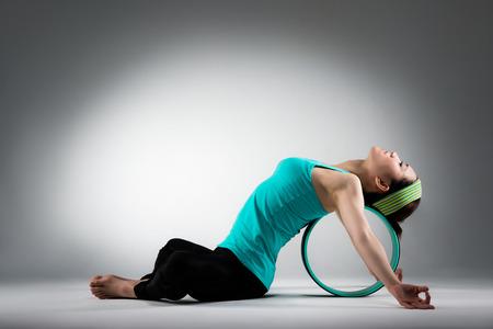 elegante vrouwelijke gymnastiekspeler die op pilatesring ligt die de zachtheid van de lichaamsmeditatie uitrekt workout wanneer zij op grijze muurachtergrond zit.