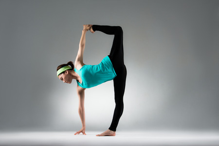 young gymnastics athlete pull legs single foot standing on gray wall background show yoga forging posture in the fitness studio.