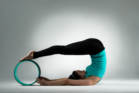 bodybuilding lecturer hand pull pilates ring and body raised legs against wheel forging body softness in gray wall background studio.