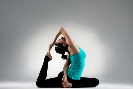 beautiful fitness lecturer hands crossed to pull legs and head up for forging softness and muscle development in gray wall background performance yoga gesture. Banco de Imagens