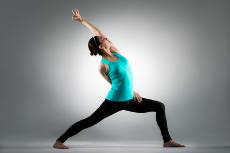 beautiful yoga lady using lunge posing standing in grey background and hand stretching workout body.