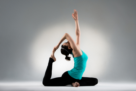 professional yoga female student sitting on floor pull feet stretch in back and hand extends to top in gray wall background fitness center studio room. Stok Fotoğraf