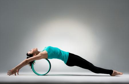 ピラティス フィットネスに横たわった若い体操少女はホイールのリングとヨガ スタジオ教室の灰色の壁背景床で体をリラックスします。