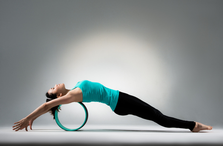 young gymnastics girl lying on pilates fitness ring wheel and relax body in gray wall background floor in yoga studio classroom. Banque d'images