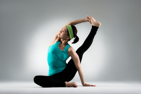 professional yoga teacher stretch body and hands pull feet forging body softness balance in gray wall background in studio.