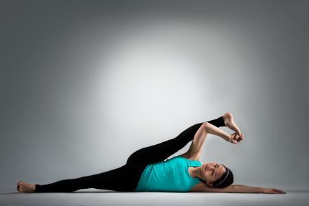 pretty female fitness teacher lying on floor doing yoga and using hand pulling leg to stretching body workout in grey background.
