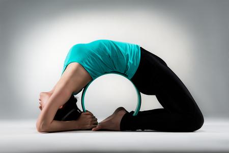 professionelle Yoga-Dame zurück um Pilates Ring liegen auf grauem Hintergrund Boden und zeigt perfekte Fitness-Haltung im Studio.