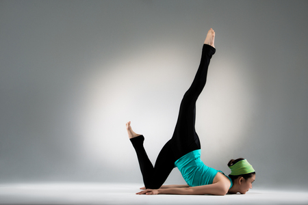 sexy fitness female athlete upper body leaning against floor and legs stretched upward show perfect yoga gesture forging body on gray background.
