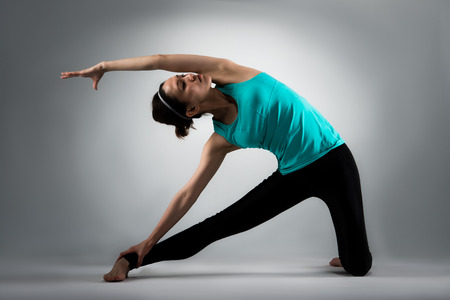 beautiful yoga fitness woman workout body in grey background and one leg kneeling on floor stretching to training softness.