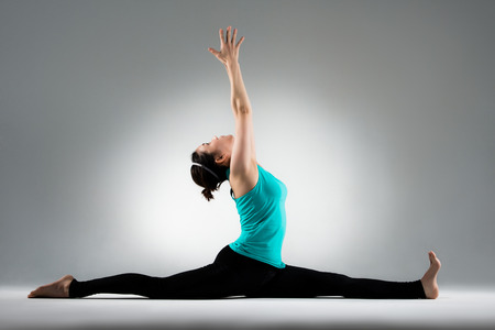 pretty yoga student split her legs and hands up to extend stretch body meditation in gray background in personal fitness studio.