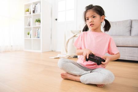 어린 소녀 자식 게임 조이스틱을 심각 하 게보고 문제를 해결할 수없는 걱정 된 frighted 비디오 게임을 들고 거실 바닥에 앉아 해결할 수 없습니다. 스톡 콘텐츠