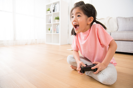 leisurely children little girl holding joystick happy play video game and performed stimulate tension expression sitting on living room wooden floor.