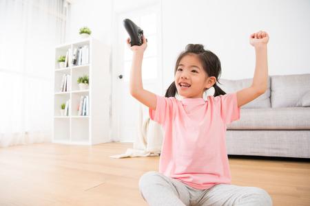 매력적인 어린 소녀 아이 온라인 비디오 게임 승리 승리를 축 하 하 고 집에서 나무 바닥에 앉아 조이스틱 컨트롤러를 들고 그녀의 손을 제기.
