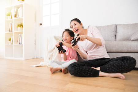 good relationship cute little girl with young mother using joystick playing video game sitting together in living room wooden floor enjoying family holiday.