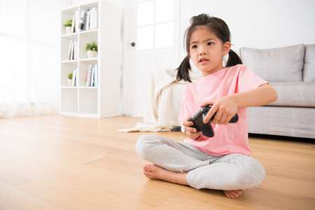 beautiful kid girl children using control joystick seriously playing video game and body swings with game sitting on wooden floor at home. Stock Photo
