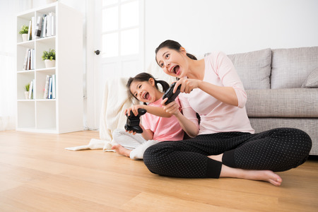beautiful little girl children and pretty housewife mom leisurely relax playing tv video game and holding controller with game to move body sitting together in family lounge wood floor.