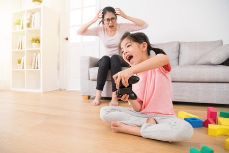 happy young little girl children holding controller playing video games in living room wooden floor with many colorful toy while her mad mother very angry showing crazy emotion on sofa.