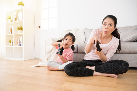 young little daughter and beautiful mom sitting on living room wood floor using joystick controller playing video game and make same expression and action at family vacation.