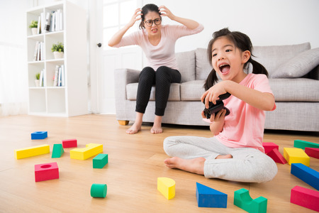 beautiful cute excited daughter playing video games by controller with many messy toy sitting on wooden floor with angry woman mother looking her in living room on background sofa.