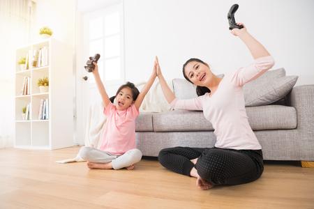 geluk familie gelukkige moeder en opgewonden dochter zitten in de woonkamer houten vloer samen klappen en houd de controller opgeheven handen voor vieren videogames winnen. Stockfoto