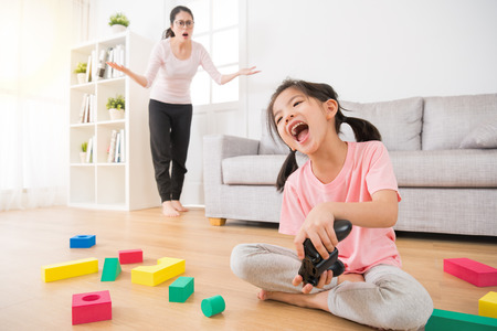 cute little girl children with a lot of messy toys on wood floor happy holding joystick play video games when her mother found stunned looking at her and make incredible gestures in background. Stock Photo