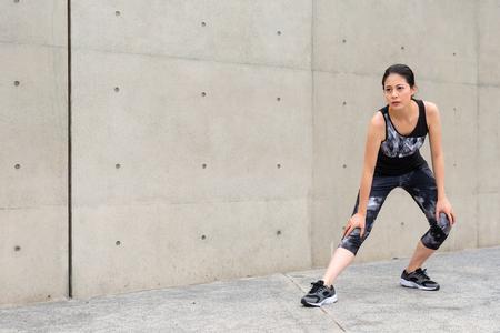 jonge vrouw staande op buiten grijze muur achtergrond maken benen opwarmen en strekken voeten met knieën voorbereiden lopen in de stad weg op vakantie training tijd. Stockfoto