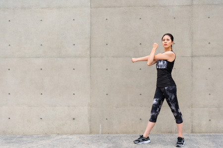 leisurely girl standing on gray wall outdoor walkway hands cross making arms warmup and look at distance thinking training running goal in weekend. Stok Fotoğraf