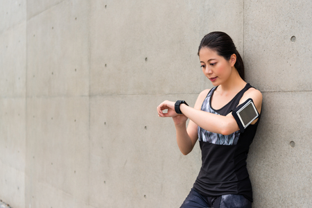 beautiful professional female athlete wearing smart watch using sports app record personal heart rate and grades ready for running training on gray background. Stock Photo - 84061194