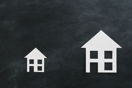 high angle view photo of estate investment advertising with two different size paper house model isolated on black chalkboard background.