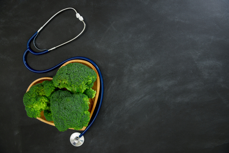 shaped: high angle view photo of hospital equipment stethoscope with green broccoli vegetable in wooden heart shaped plate isolated on blackboard. Stock Photo
