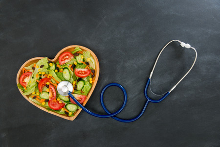 medical device stethoscope touching fresh healthy food vegetable in wooden heart shaped plate showing healthcare concept on blackboard with high angle photo. Banco de Imagens