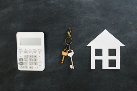 high angle view photo of calculator tool with key showing buying new house concept isolated on black chalkboard background. Archivio Fotografico