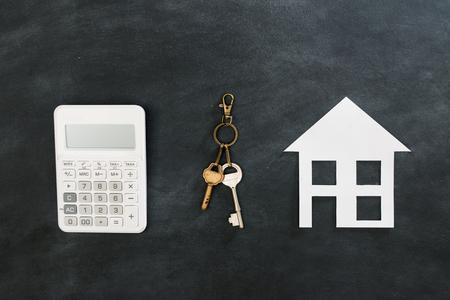 hoge hoek weergave foto van rekenmachine hulpmiddel met sleutel weer gegeven: kopen nieuwe huis concept geïsoleerd op een zwarte schoolbord achtergrond.