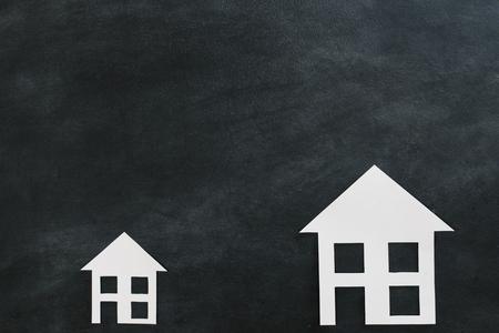 papieren huis model geïsoleerd op blackboard achtergrond met hoge hoek weergave foto. Stockfoto