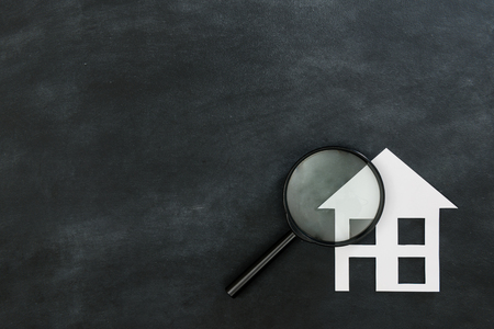 magnifier searching new house concept isolated on chalkboard background with high angle view photo. Archivio Fotografico