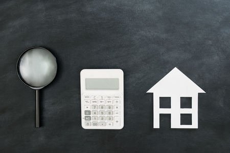 magnifier tool and calculator with paper house model presenting on black chalkboard background showing estate investment concept.