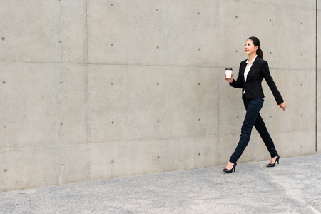 beautiful suit right woman holding white coffee paper cup walking in office outside gray wall background walkway relaxing at work free time. Stok Fotoğraf
