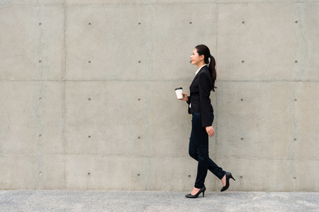 confident business lady walking on gray wall background sidewalks outdoor corridor holding hot espresso coffee cup ready to go office meeting.