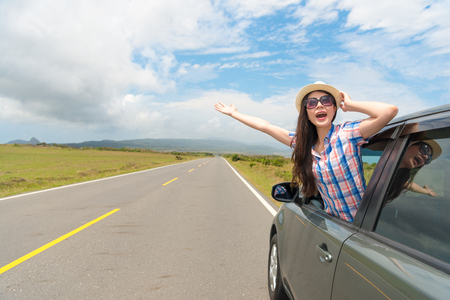 smiling girl holding hat wearing sunglasses looking country scenery in car window and making showing gestures enjoying travel holiday.