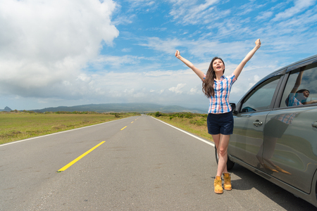 slim elegant female traveler stopping car on asphalt roadside and standing next to car raised hands enjoying local countryside scenery.