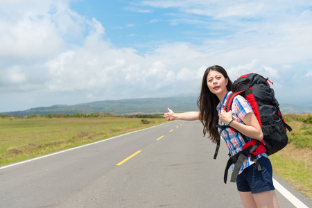 smiling female traveler standing on road making thumb up gesture for hitchhiking hoping find passing car carrying her to transfer station when she in travel.